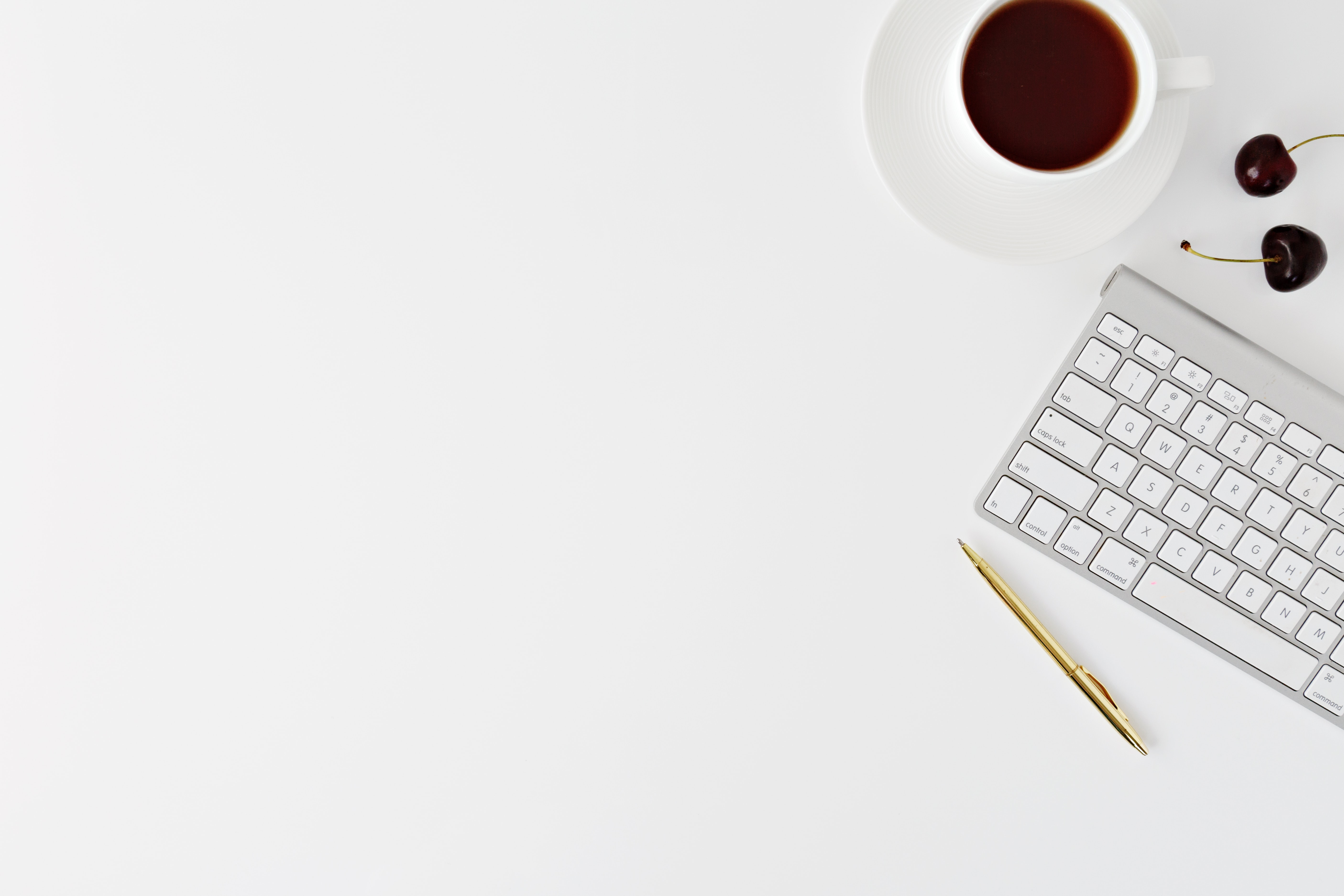 A cup of coffee, two cherries, the magic keyboard and a pencil